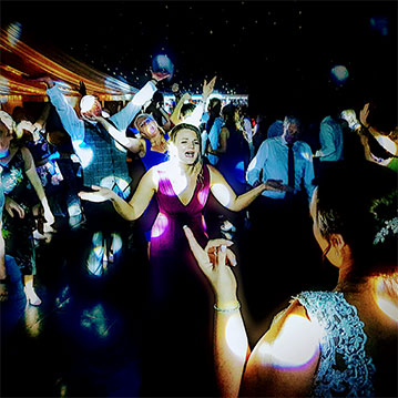 Chippenham Park wedding guests wave hands in the air during DJ set.