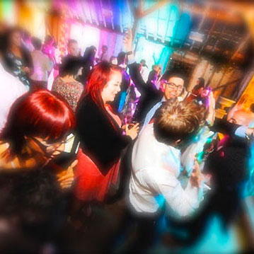 Suffolk Wedding DJ, Coloured venue uplighting at Preston Priory Barn during wedding party with guests dancing.