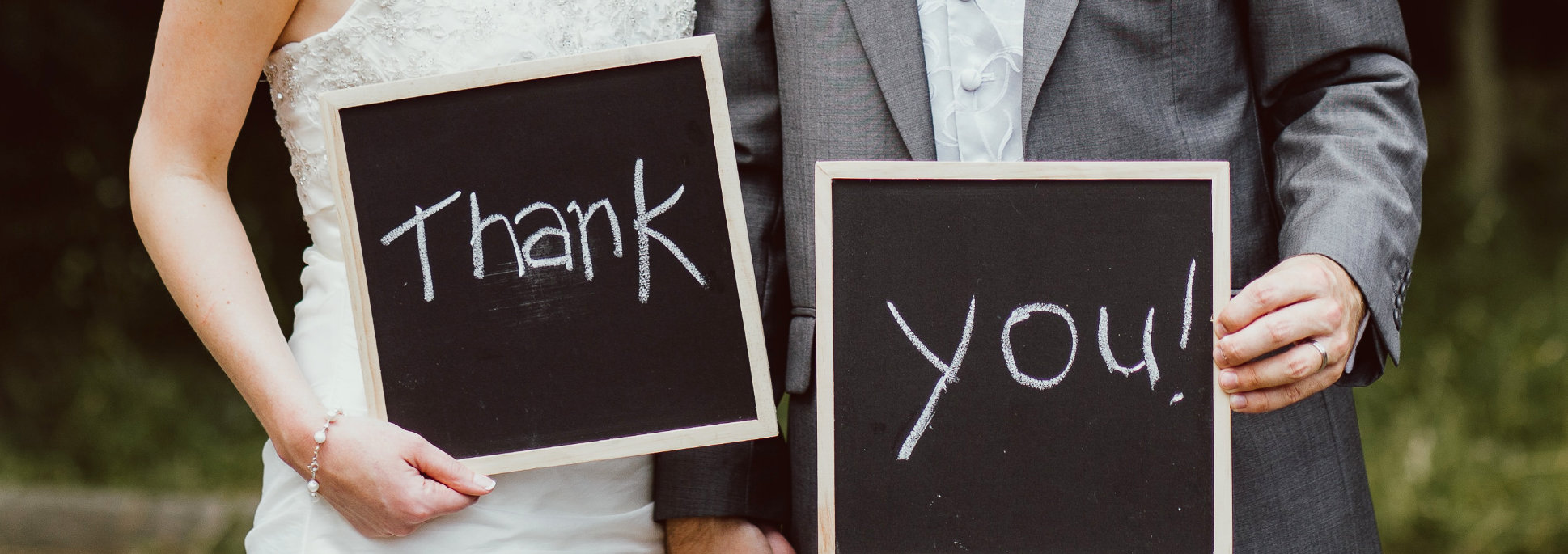 Wedding couple hold up Thank You signs written on chalk boards.