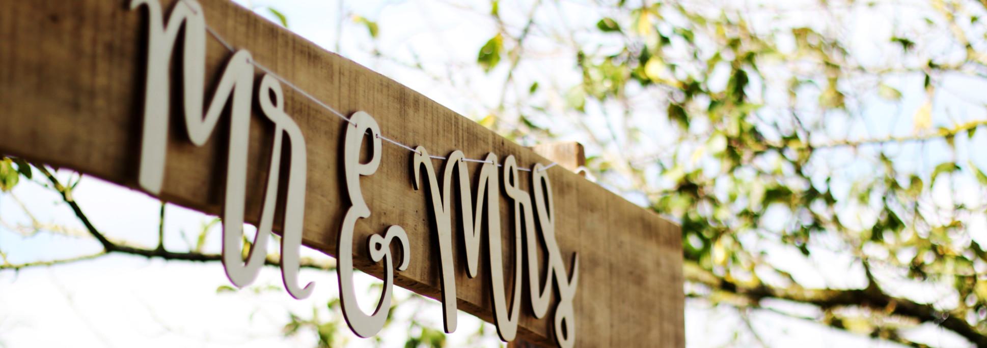 Mr & Mrs wooden wedding hanging sign under trees.