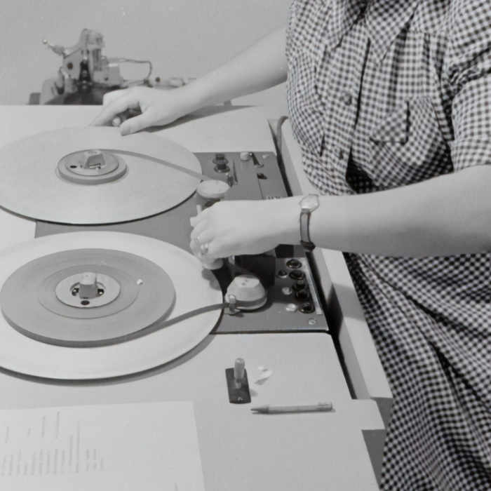 Lady using old fashioned tape reel desk